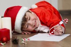 Παιδί σε ένα κοστούμι Άγιου Βασίλη που γράφει μια επιστολή Στοκ Εικόνες