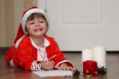Παιδί σε ένα κοστούμι Άγιου Βασίλη που γράφει μια επιστολή Στοκ Εικόνα