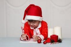 Παιδί σε ένα κοστούμι Άγιου Βασίλη που γράφει μια επιστολή Στοκ Φωτογραφία