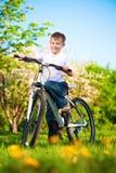 Παιδί σε ένα πράσινο πάρκο σε ένα ποδήλατο Στοκ φωτογραφίες με δικαίωμα ελεύθερης χρήσης
