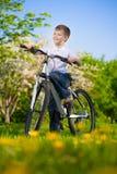 Παιδί σε ένα πράσινο πάρκο σε ένα ποδήλατο Στοκ Εικόνες