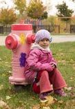 Παιδί σε ένα ρόδινο στόμιο υδροληψίας πυρκαγιάς Στοκ Εικόνες