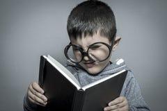 Παιδί, σκοτεινός-μαλλιαρός νέος σπουδαστής που διαβάζει ένα αστείο βιβλίο, που διαβάζει το α Στοκ Εικόνες
