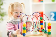Παιδί στα eyeglases που παίζει το ζωηρόχρωμο παιχνίδι στο σπίτι Στοκ φωτογραφία με δικαίωμα ελεύθερης χρήσης