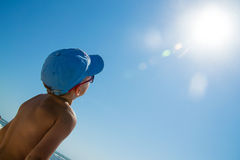 Παιδί στην μπλε ΚΑΠ και γυαλιά ηλίου που κοιτάζουν στον ήλιο πλησίον Στοκ Εικόνες