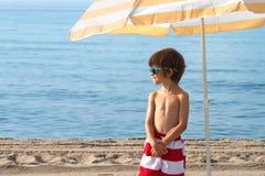 Παιδί στην παραλία κάτω από την ομπρέλα με τα γυαλιά ηλίου που κοιτάζουν Στοκ Εικόνες