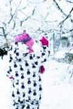 Παιδί στη χιονώδη ημέρα Κοριτσάκι στο άσπρο snowsuite και ρόδινο καπέλο, γάντια μποτών στο χειμερινό πάρκο χιονιού Στοκ Φωτογραφίες
