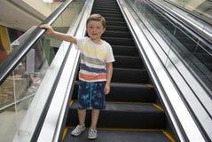 Παιδί στο εμπορικό κέντρο που στέκεται στην κίνηση της κυλιόμενης σκάλας Στοκ Εικόνες