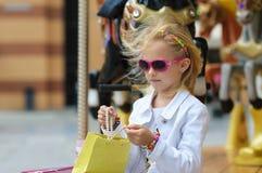 Παιδί στο ιπποδρόμιο με τις πλήρεις τσάντες αγορών Στοκ εικόνα με δικαίωμα ελεύθερης χρήσης