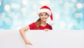 Παιδί στο καπέλο αρωγών santa με τον κενό λευκό πίνακα Στοκ Εικόνες
