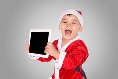 Παιδί στο καπέλο Χριστουγέννων με την ταμπλέτα στοκ εικόνες με δικαίωμα ελεύθερης χρήσης