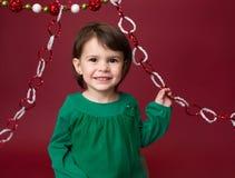 Παιδί Χριστουγέννων: Ευτυχές κορίτσι στο κόκκινο υπόβαθρο στοκ φωτογραφίες