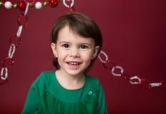 Παιδί Χριστουγέννων: Ευτυχές κορίτσι στο κόκκινο υπόβαθρο στοκ φωτογραφία