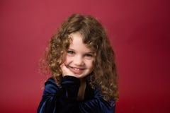 Παιδί Χριστουγέννων: Ευτυχές κορίτσι στο κόκκινο υπόβαθρο στοκ εικόνες