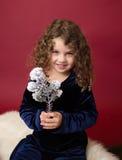Παιδί Χριστουγέννων: Ευτυχές κορίτσι στο κόκκινο υπόβαθρο στοκ εικόνα
