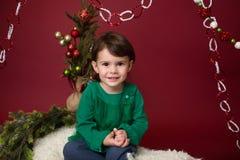 Παιδί Χριστουγέννων στο έλκηθρο ενάντια στο χριστουγεννιάτικο δέντρο με τις διακοσμήσεις στοκ εικόνες