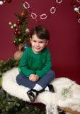 Παιδί Χριστουγέννων στο έλκηθρο ενάντια στο χριστουγεννιάτικο δέντρο με τις διακοσμήσεις στοκ φωτογραφία με δικαίωμα ελεύθερης χρήσης