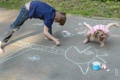 Παιδιά αμφιθαλών που παίζουν κατά τη διάρκεια chalking πεζοδρομίων στην επιφάνεια ασφάλτου Στοκ Εικόνες