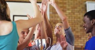 Παιδιά γυμνασίου που δίνουν υψηλά πέντε κρατώντας το τρόπαιο στο γήπεδο μπάσκετ απόθεμα βίντεο