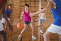 Παιδιά γυμνασίου που παίζουν την καλαθοσφαίριση στο δικαστήριο Στοκ φωτογραφία με δικαίωμα ελεύθερης χρήσης