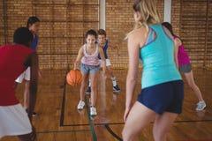 Παιδιά γυμνασίου που παίζουν την καλαθοσφαίριση στο δικαστήριο Στοκ Εικόνες