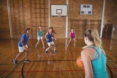Παιδιά γυμνασίου που παίζουν την καλαθοσφαίριση στο δικαστήριο Στοκ Φωτογραφία