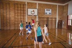Παιδιά γυμνασίου που παίζουν την καλαθοσφαίριση στο δικαστήριο Στοκ Φωτογραφίες