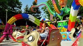 Παιδιά και γονείς που έχουν τη διασκέδαση στο δημόσιο γύρο λούνα παρκ νεολαιών φιλμ μικρού μήκους