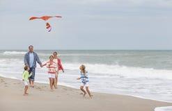 Παιδιά κοριτσιών οικογενειακών γονέων που πετούν τον ικτίνο στην παραλία Στοκ Φωτογραφίες