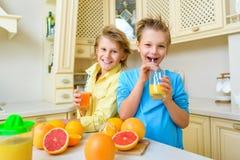 Παιδιά με τα εσπεριδοειδή Τα αγόρια πίνουν το φρέσκο πορτοκάλι Στοκ φωτογραφίες με δικαίωμα ελεύθερης χρήσης