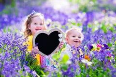 Παιδιά με τα λουλούδια και τον πίνακα κιμωλίας Στοκ Εικόνα