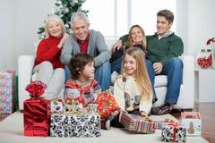 Παιδιά με τα χριστουγεννιάτικα δώρα ενώ οικογένεια Στοκ φωτογραφία με δικαίωμα ελεύθερης χρήσης