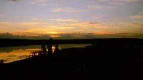 Παιδιά με την περιστροφή πατέρων στην ακτή στο ηλιοβασίλεμα απόθεμα βίντεο