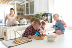 Παιδιά με τη μητέρα της που προετοιμάζει τα μπισκότα, μεγάλη οικογένεια casua Στοκ Εικόνα