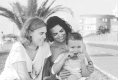 Παιδιά με τη συνεδρίαση και το γέλιο mom Αγόρι που μασά ένα ραβδί Στοκ Φωτογραφίες
