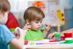 Παιδιά με τον άργιλο παιχνιδιού στο σπίτι Στοκ εικόνα με δικαίωμα ελεύθερης χρήσης
