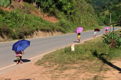 Παιδιά με τον ήλιο που προστατεύει τις ομπρέλες που περπατούν κάτω από την οδό στοκ φωτογραφία με δικαίωμα ελεύθερης χρήσης