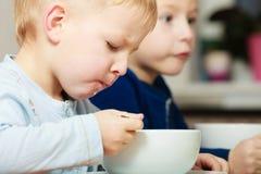 Παιδιά παιδιών αγοριών που τρώνε το γεύμα προγευμάτων νιφάδων καλαμποκιού στον πίνακα στοκ εικόνα