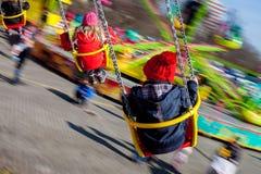 Παιδιά, που έχουν τη διασκέδαση σε έναν γύρο ιπποδρομίων αλυσίδων ταλάντευσης Στοκ Εικόνες