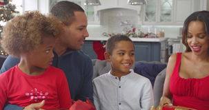 Παιδιά που δίνουν τα δώρα Χριστουγέννων γονέων στο σπίτι - τινάζουν τις συσκευασίες και προσπαθούν να υποθέσουν τι είναι μέσα απόθεμα βίντεο