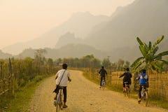 Παιδιά που ανακυκλώνουν, ηλιοβασίλεμα στα βουνά ασβεστόλιθων Vang Vieng, Λάος στοκ φωτογραφίες