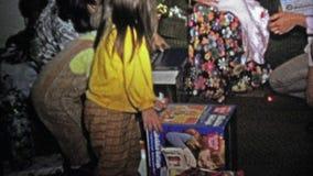 1973: Παιδιά που ανοίγουν τα παιχνίδια δώρων Χριστουγέννων με τα φορέματα λουλουδιών γύρω απόθεμα βίντεο