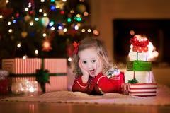 Παιδιά που ανοίγουν τα χριστουγεννιάτικα δώρα στην εστία Στοκ φωτογραφίες με δικαίωμα ελεύθερης χρήσης