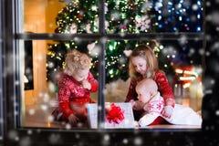 Παιδιά που ανοίγουν τα χριστουγεννιάτικα δώρα στην εστία Στοκ Εικόνες
