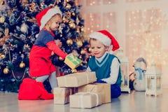 Παιδιά που ανοίγουν τα χριστουγεννιάτικα δώρα στο διακοσμημένο καθιστικό Στοκ φωτογραφία με δικαίωμα ελεύθερης χρήσης