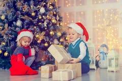 Παιδιά που ανοίγουν τα χριστουγεννιάτικα δώρα στο διακοσμημένο καθιστικό Στοκ Εικόνες