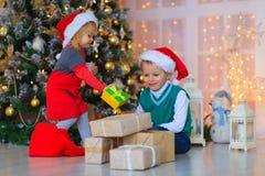 Παιδιά που ανοίγουν τα χριστουγεννιάτικα δώρα στο διακοσμημένο καθιστικό Στοκ εικόνες με δικαίωμα ελεύθερης χρήσης