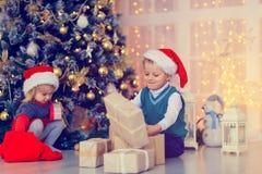 Παιδιά που ανοίγουν τα χριστουγεννιάτικα δώρα στο διακοσμημένο καθιστικό Στοκ φωτογραφίες με δικαίωμα ελεύθερης χρήσης
