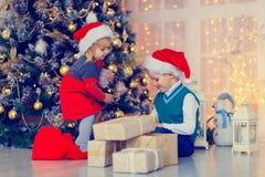Παιδιά που ανοίγουν τα χριστουγεννιάτικα δώρα στο διακοσμημένο καθιστικό Στοκ εικόνα με δικαίωμα ελεύθερης χρήσης
