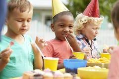 Παιδιά που απολαμβάνουν την υπαίθρια γιορτή γενεθλίων από κοινού Στοκ Εικόνες